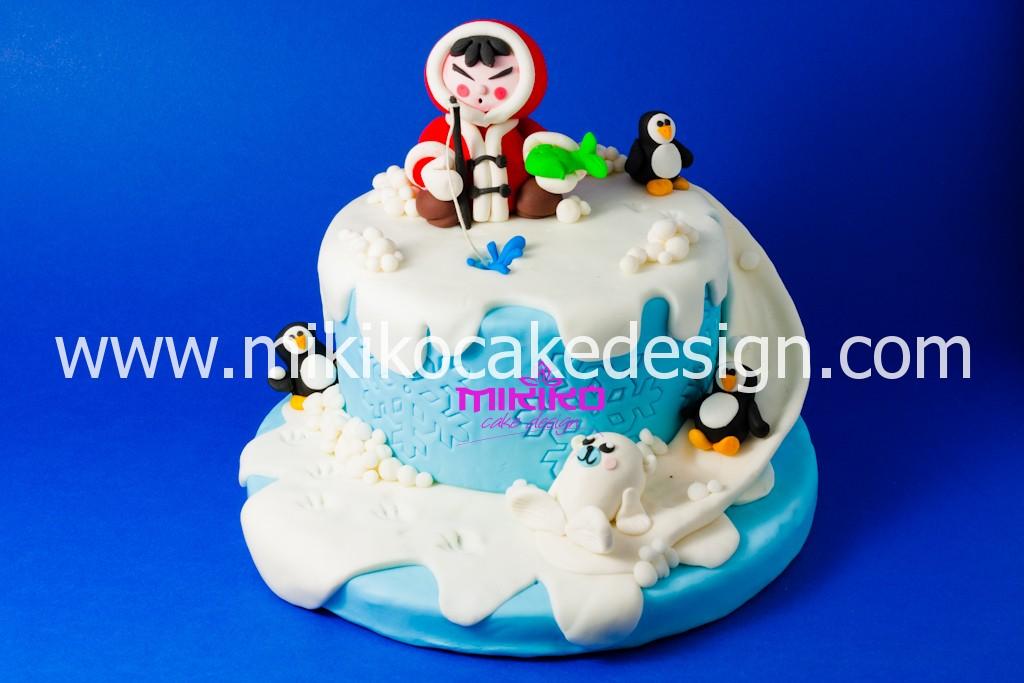 Immagine decorazione una torta per il periodo invernale decorata in pasta di zucchero con eschimese e pinguini